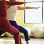 """women practicing yoga, in """"warrior one"""" asana"""