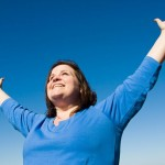 woman with outstretched arms smiling victoriously